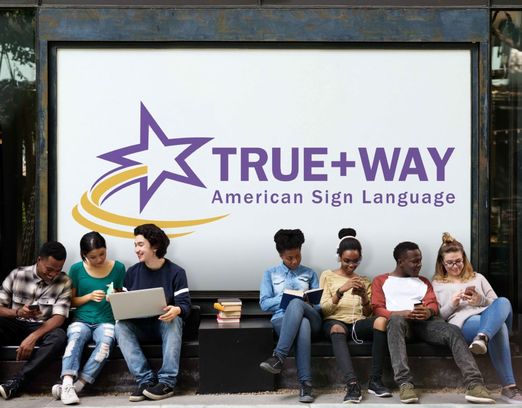 Seven diverse students sit on a bench with a large banner behind them with the TWA logo. Each student is chatting, using their phone or laptop.